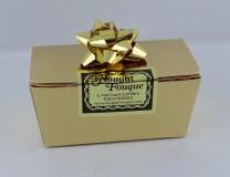 Petite boîte dorée contenant 30g de nougat soit deux petites bouchées de nougat noir; une bouchée de nougat blanc Provence et une bouchée de nougat blanc Félibres.